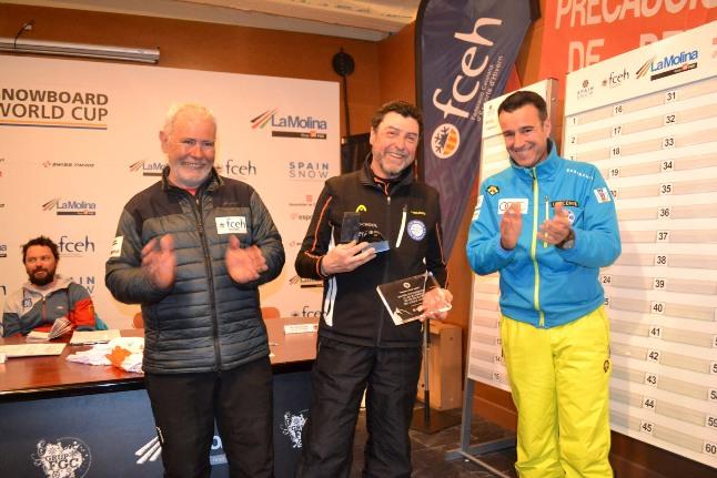 Un representante de La Molina Club d'Espots recibe el galardón con Oscar Cruz, presidente de la FCEH y May Peus, de la RFEDI