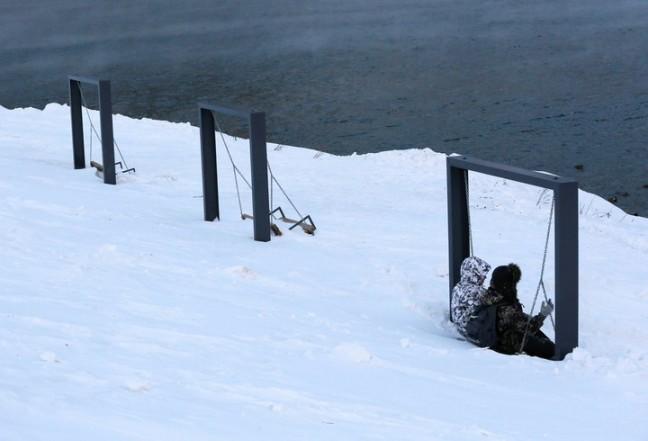 Un parque infantil literalmente colgado por la nieve