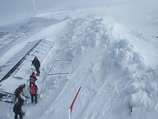 Unos operarios sacan la nieve de un edificio en Sierra de Béjar-La Covatilla
